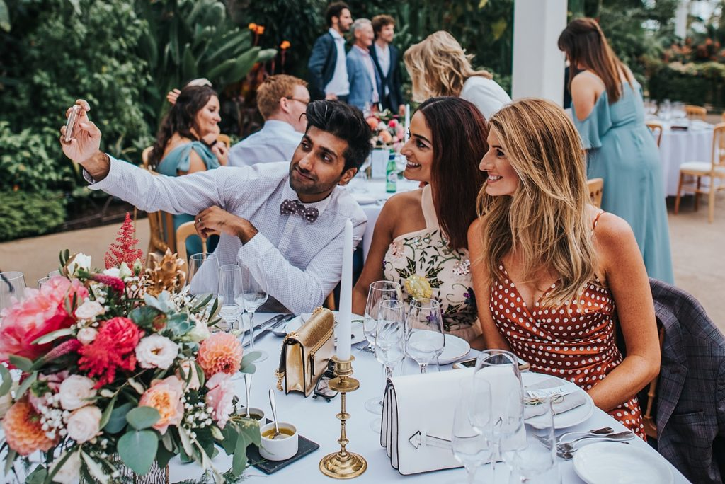 3 wedding guests taking a selfie at table