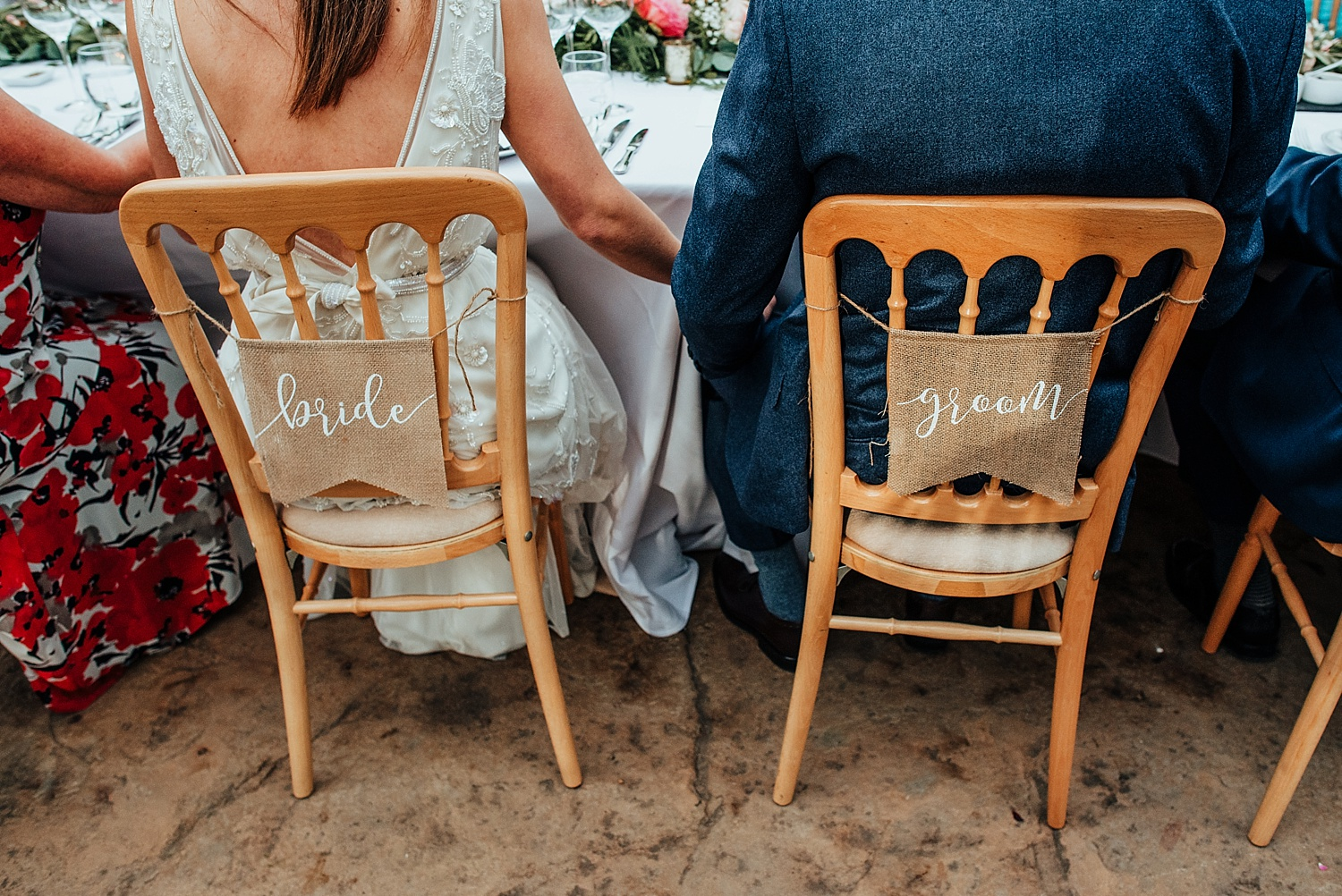 bride and groom sat on chairs with signs on back