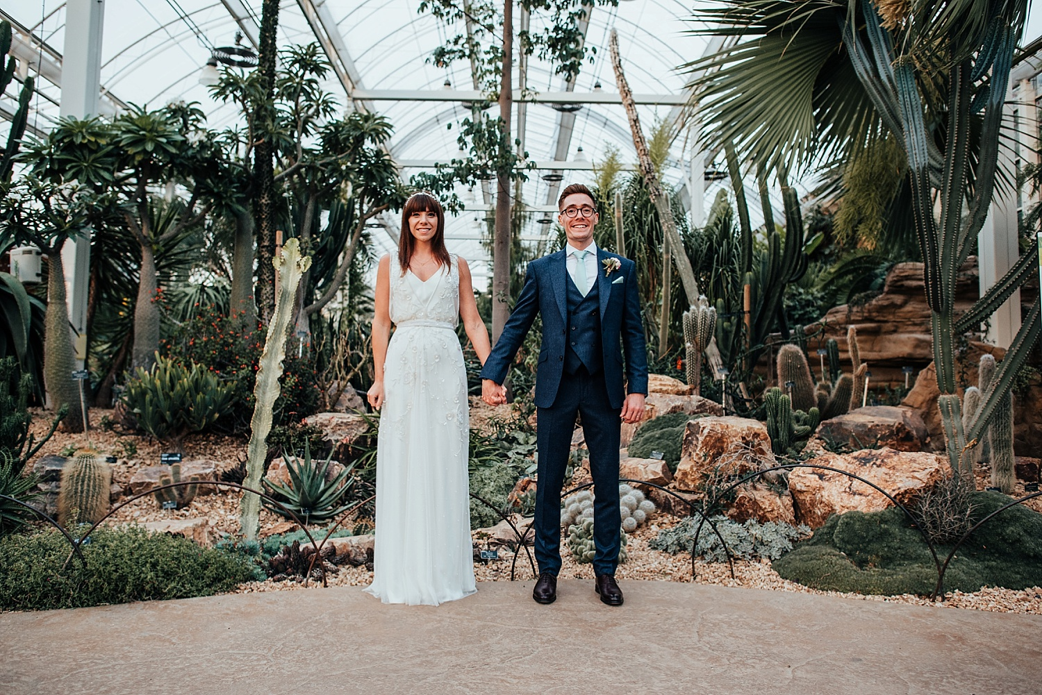 bride and groom holding hands by cactus inside RHS Wisley Glasshouse