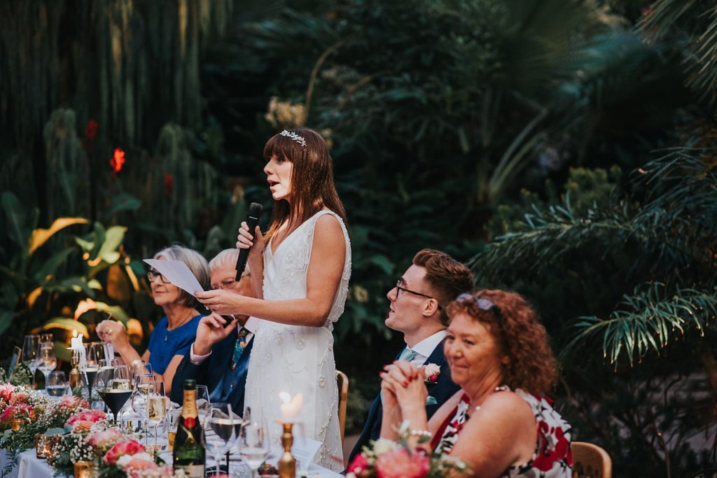 bride giving speech from top table inside RHS Wisley glasshouse