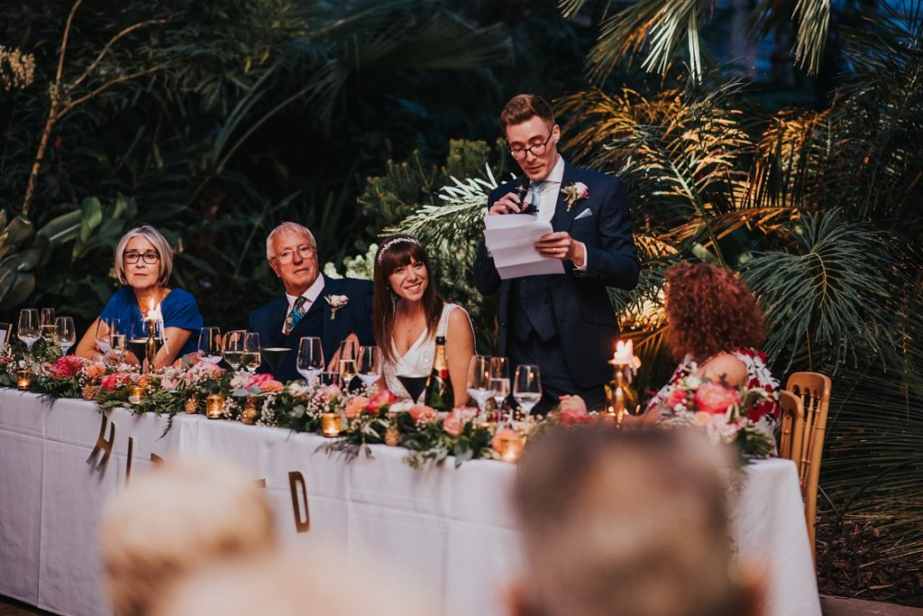groom giving speech from top table inside RHS Wisley glasshouse