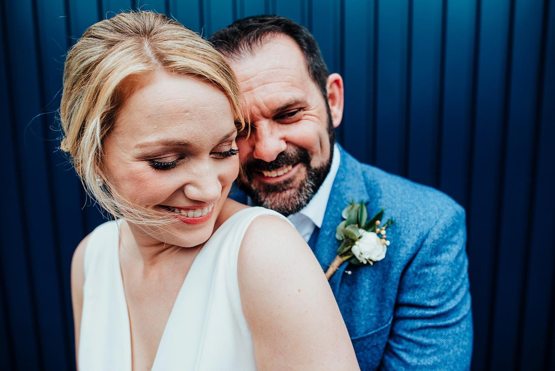 bride and groom standing in front of blue door Bombay Sapphire Wedding