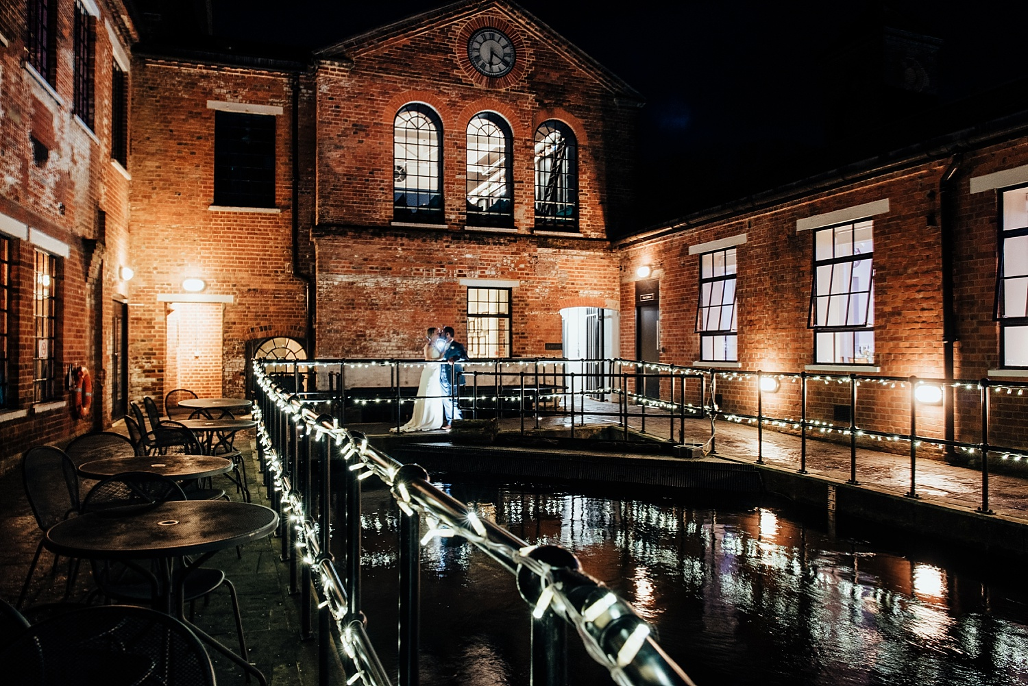 bride and groom standing in dark outside Bombay Sapphire Wedding