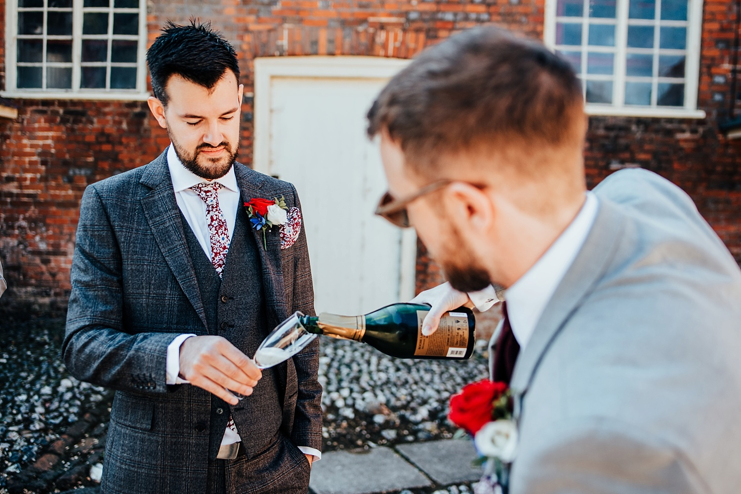 Groom pouring champaign at Stanlake Park