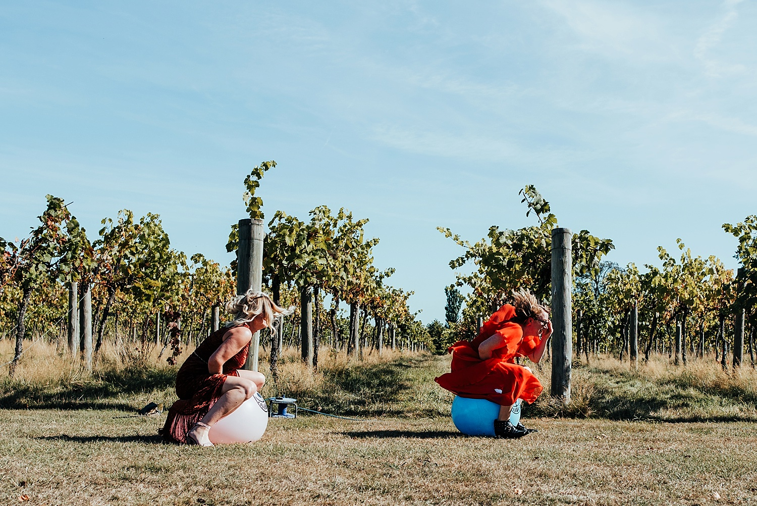 two woman bouncing on space hoppers in vineyard Stanlake Park