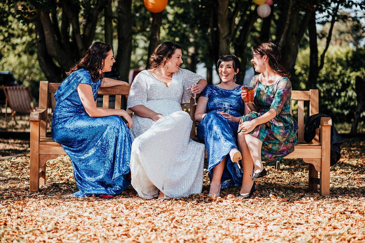 bride and guests talking on bench at Stanlake Park