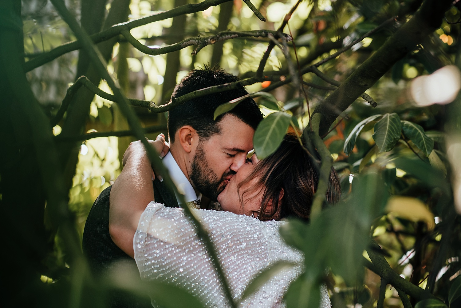 bride and groom kissing in bushes of Stanlake Park