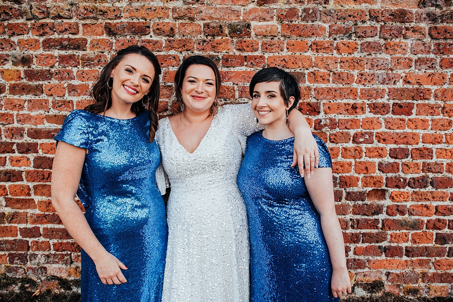 bride and bridesmaids in blue sparkly dresses at Stanlake Park