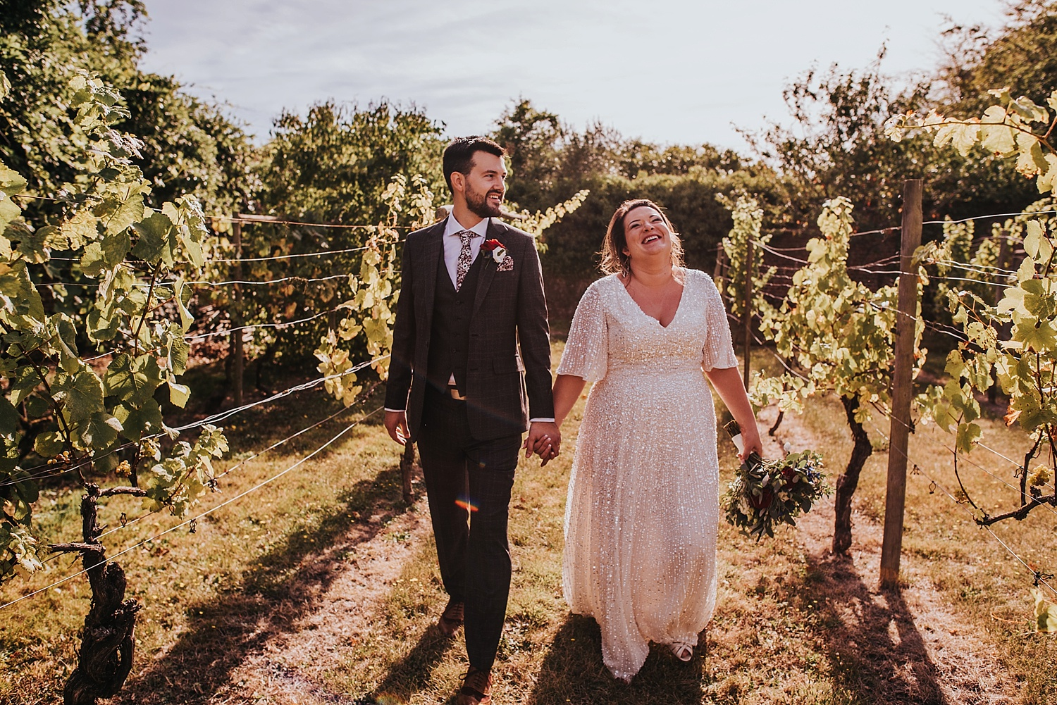 Bride and groom walking hand in hand through vineyard at Stanlake Park