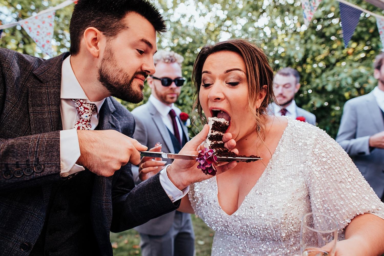 bride eating wedding cake off a knife at Stanlake Park
