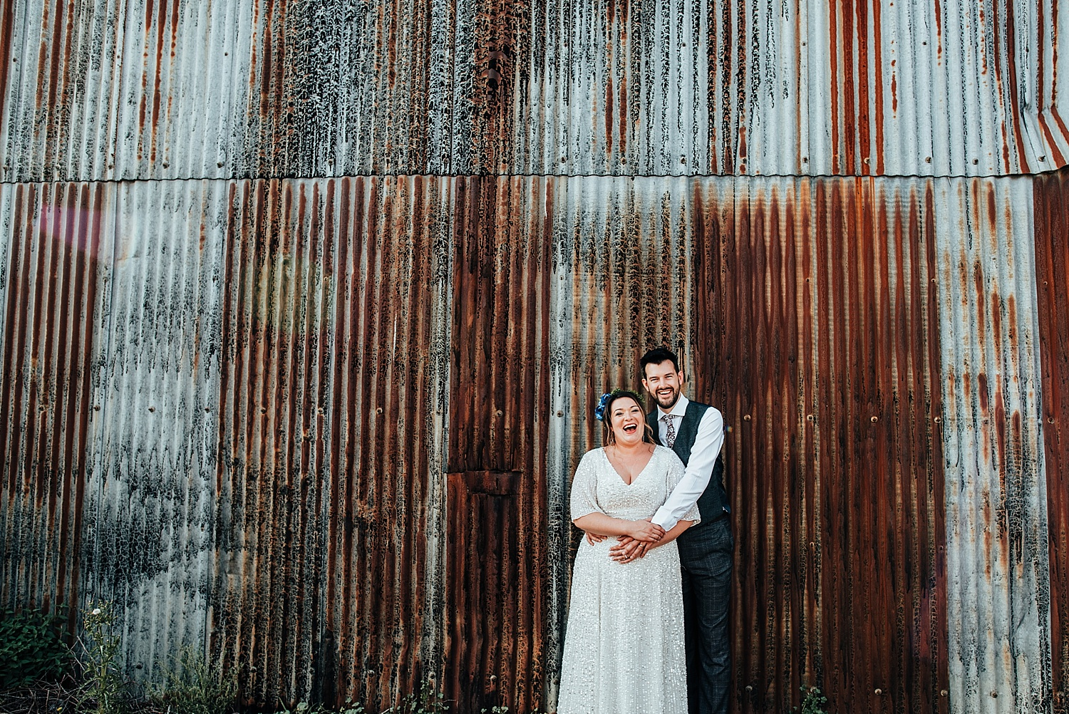 bride and groom standing by barn Stanlake Park