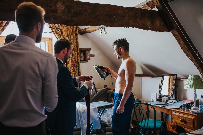 man ironing shirt Huntstile Organic Farm Wedding