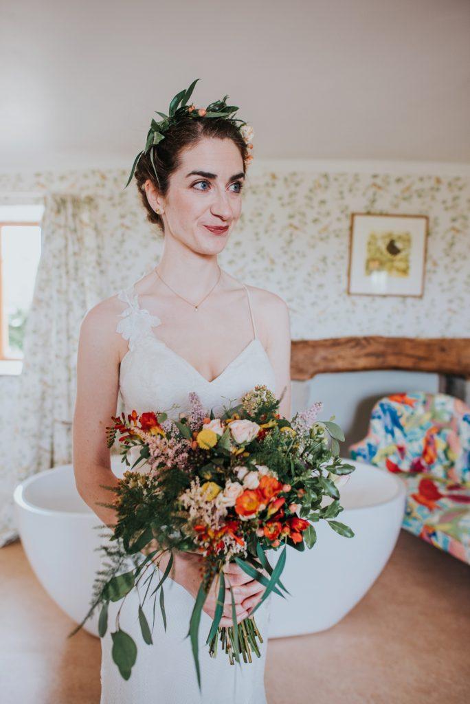 bride holding colourful wild flower wedding bouquet at huntstile farm