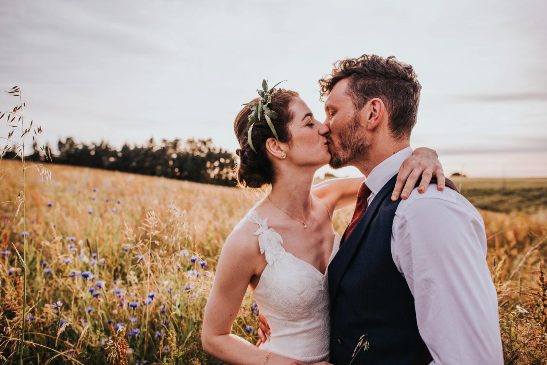 bride with flower crown and groom standing in wildflower field at huntstile organic farm