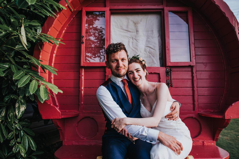 bride with flower crown and groom sitting on gypsy caravan, huntstile organic farm