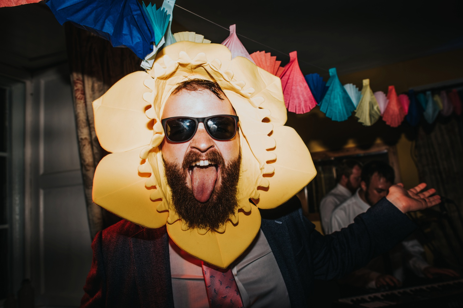 man dancing with tongue out, wearing a flower hat