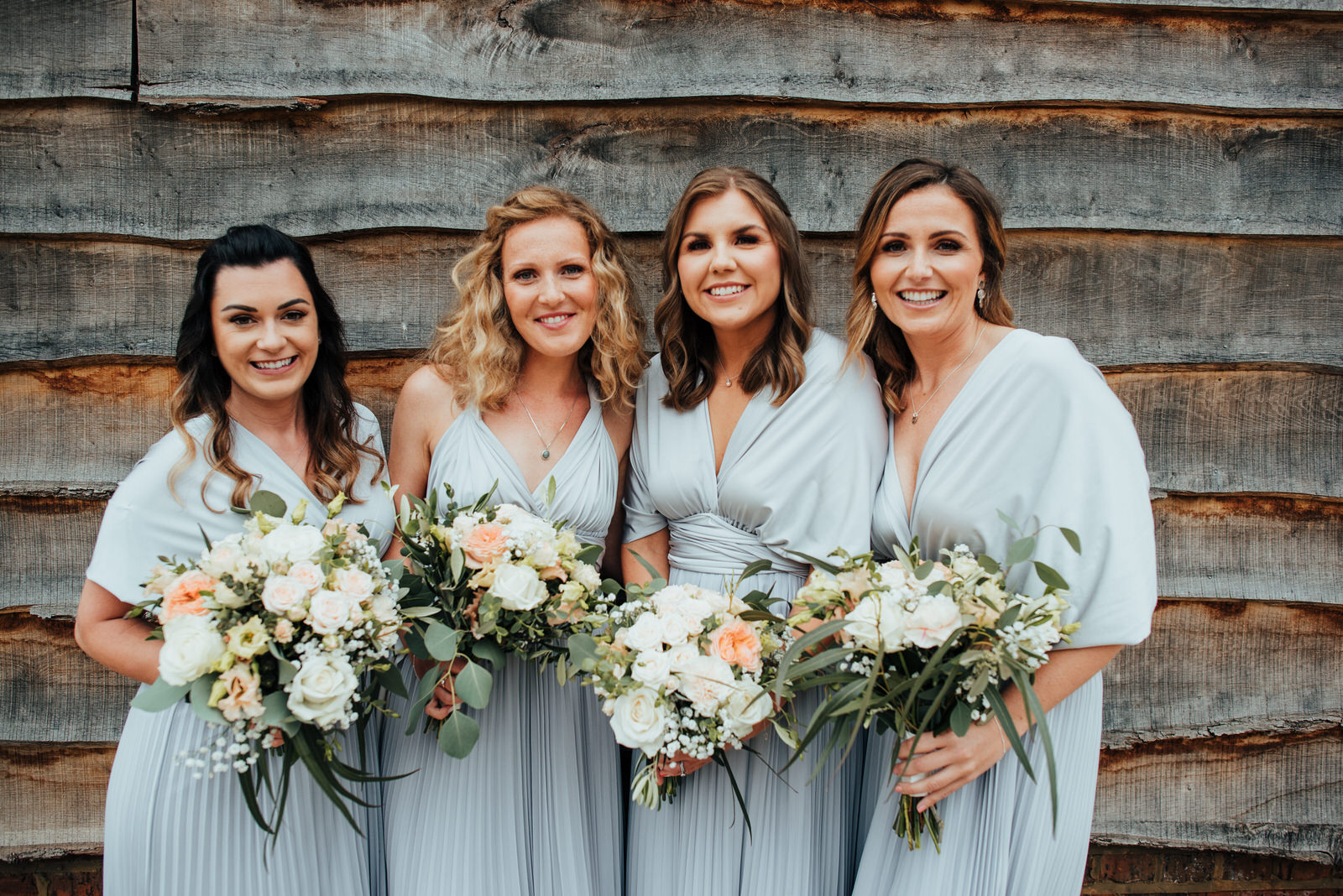 bridesmaids standing with flowers at silchester farm