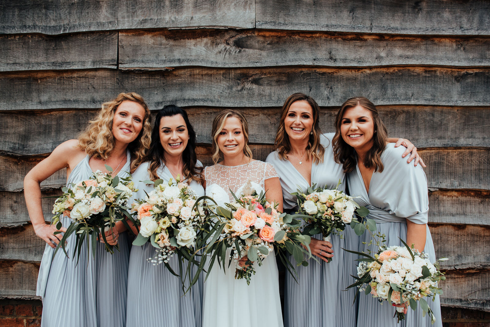 bride and bridesmaids standing in front of barn, silchester farm